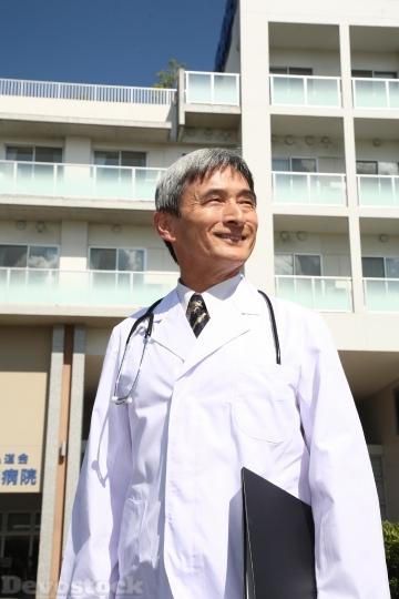 Devostock MALE DOCTOR STANDING IN FRONT OF HOSPITAL