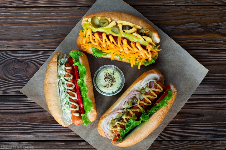 Assorted three hot dogs with sauce and salad on a wooden backgro