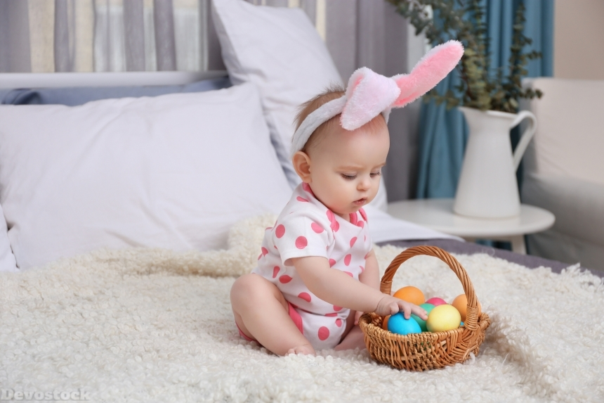 Cute funny baby with bunny ears and basket full of Easter eggs a